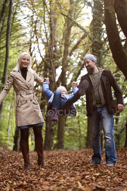 Parents playing with daughter in the autumnal forest — Stock Photo