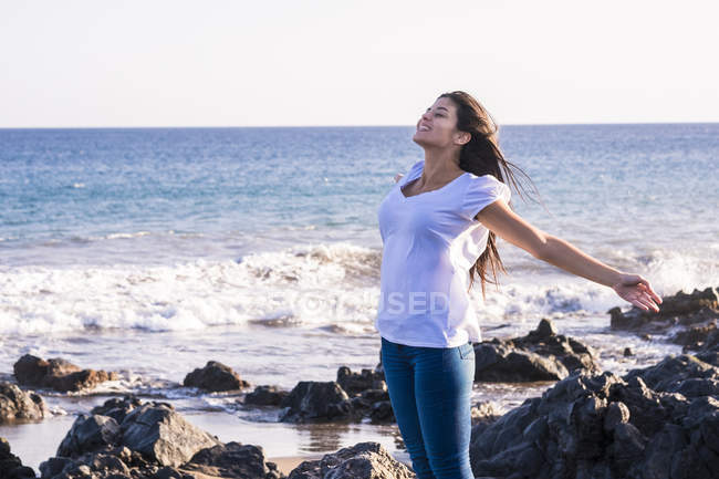 Young woman standing on beach with arms outstretched — Stock Photo