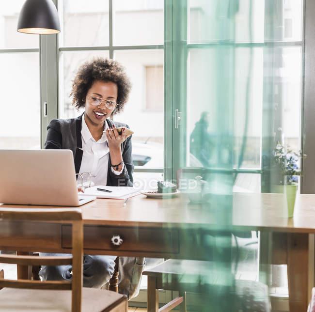 Junge Geschäftsfrau mit Handy und Laptop in einem café — Stockfoto