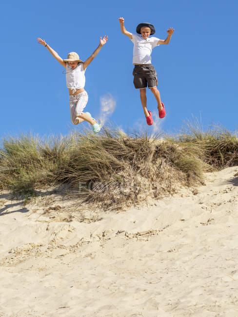 Мальчик и девочка прыгают с пляжной дюны — стоковое фото