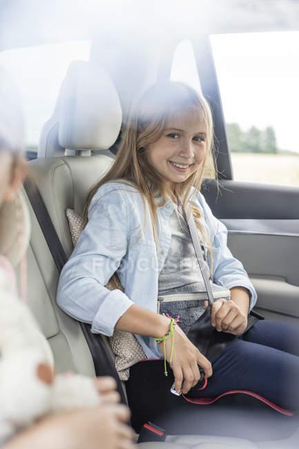 Девочка сидит в машине с сестрой и крепления ремней — стоковое фото