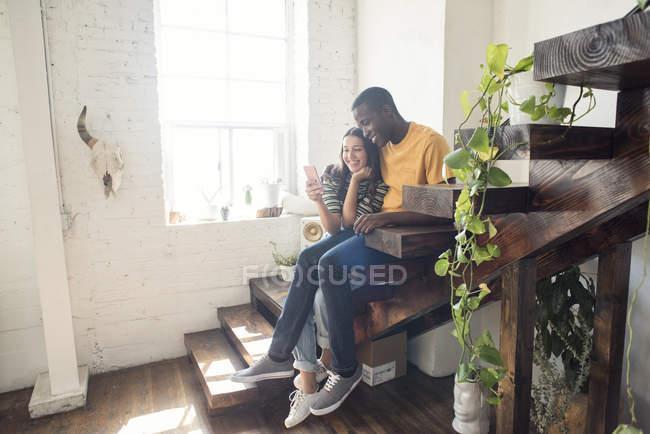 Lächelndes junges Paar, das auf einer Treppe in einem Dachboden sitzt und sein Handy teilt — Stockfoto