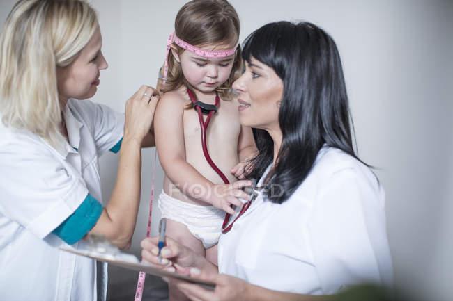 Kinderärzte untersuchen kleines Mädchen in Klinik — Stockfoto
