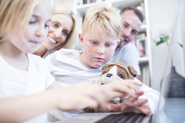 Hermano y hermana con peluche, utilizando el portátil junto con los padres en el fondo - foto de stock