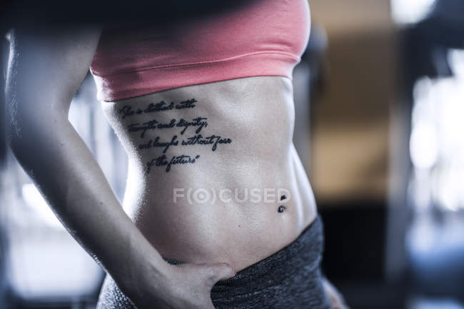Close-up of Athletic woman with strong abs and tattoo — Stock Photo