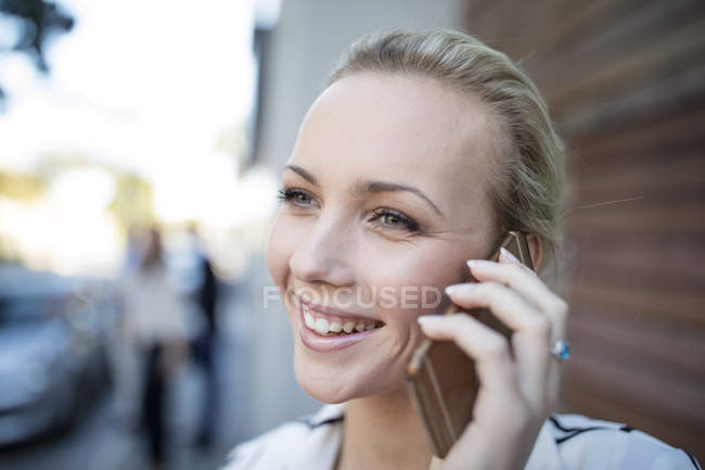 Portrait of smiling woman talking on cell phone — Stock Photo