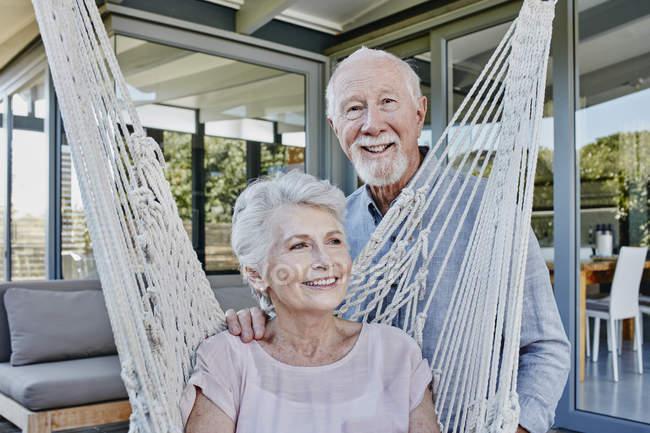 Старшая пара на террасе, женщина сидит в гамаке — стоковое фото