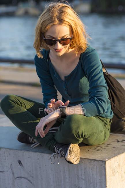Giovane donna bionda attraente seduta fuori e guardando smartwatch — Foto stock