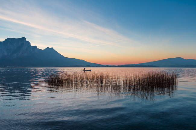 Distant view of person floating on boat in lake — Stock Photo