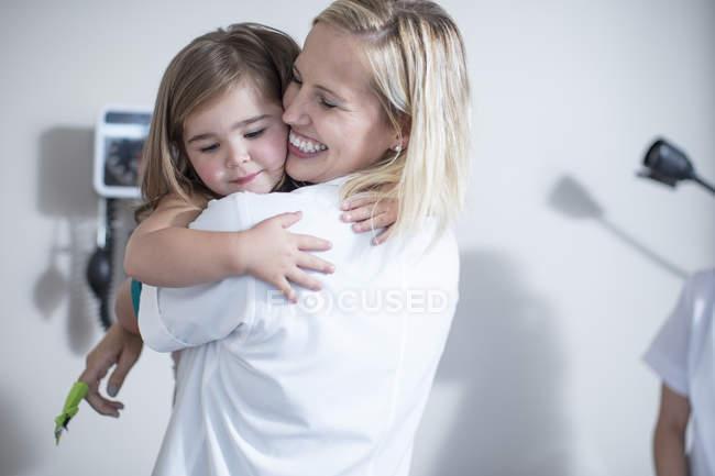 Portrait of pediatrician giving a baby girl a hug — Stock Photo