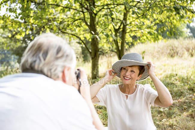 Старший мужчина фотографирование женщина в шляпе, сидя в открытом воздухе зеленый — стоковое фото