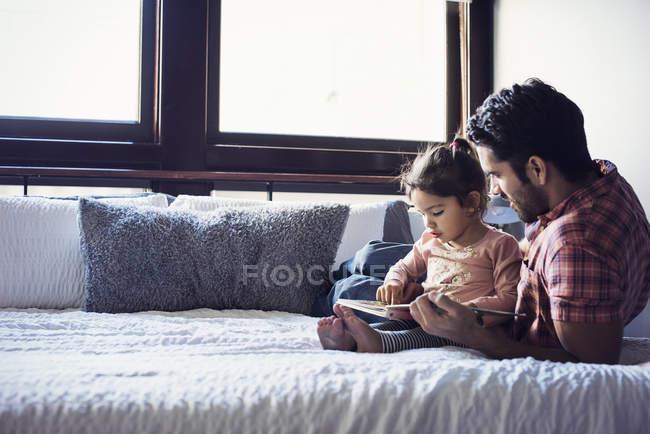 Vater mit Kleinkind-Tochter liegt gemeinsam im Bett und liest Buch — Stockfoto