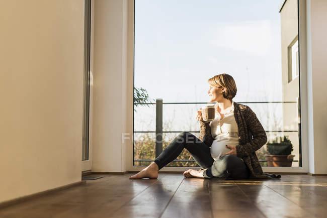 Вагітна жінка, сидячи на підлозі та проведення напій в кухоль — стокове фото