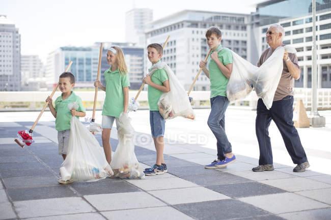 Gruppo di volontariato bambini raccolta dell'immondizia con i bastoni di lettiera — Foto stock