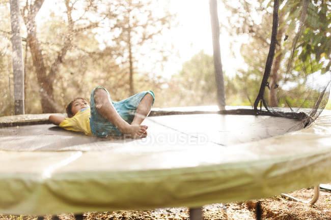 Маленький хлопчик розслабляючий на батуті в природі — стокове фото