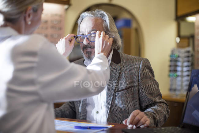 Optician helping customer to choose new spectacles — Stock Photo