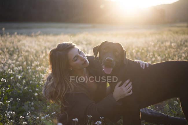 Junge Frau und ihr Hund in einem Blumenfeld in der Dämmerung — Stockfoto