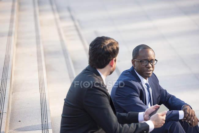 Deux hommes d'affaires assis dans les escaliers et parlant — Photo de stock