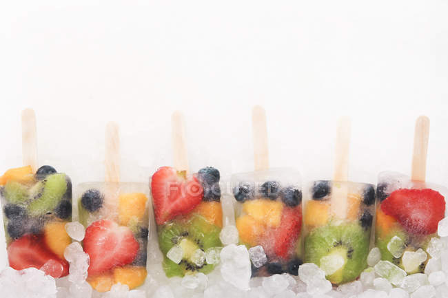 Row of colorful fruit and berry ice lollies on ice cubes — Stock Photo