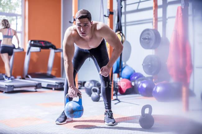Молодой человек, поднимая гири в тренажерный зал — стоковое фото