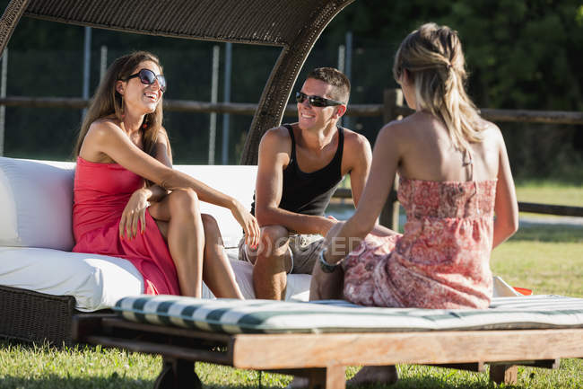 Three friends socializing in summer in garden — Stock Photo