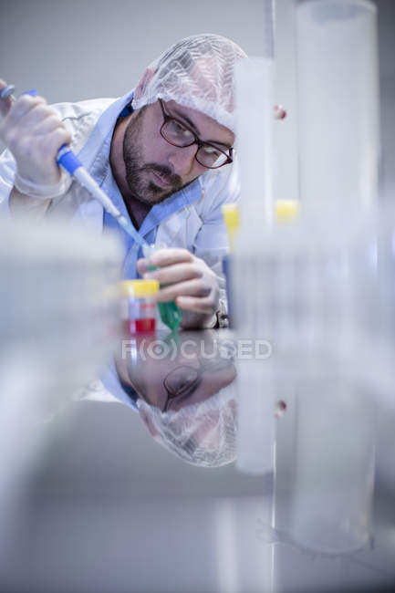 Mâle scientifique caucasien pipetage en laboratoire — Photo de stock