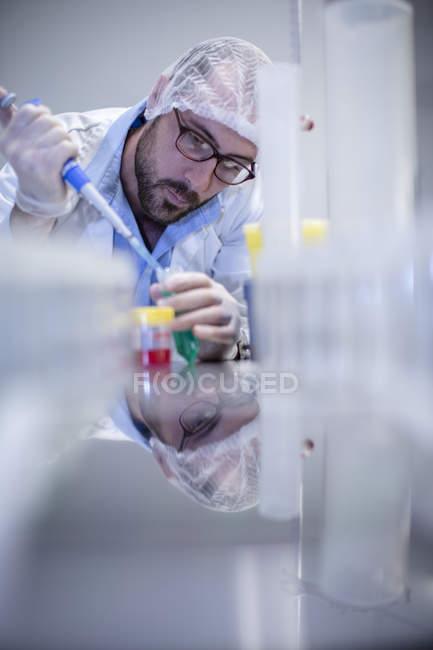 Mâle scientifique caucasien pipetage en laboratoire — Photo de stock