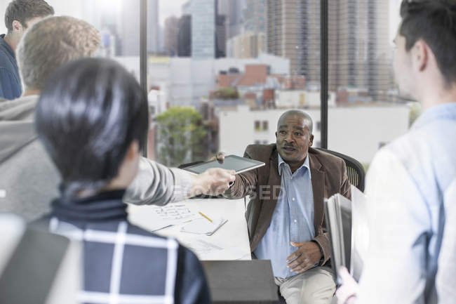 Male handing over digital tablet during discussion team meeting — Stock Photo