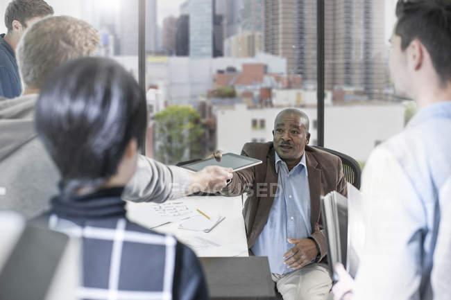 Entrega masculina tableta digital durante la reunión del equipo de discusión - foto de stock
