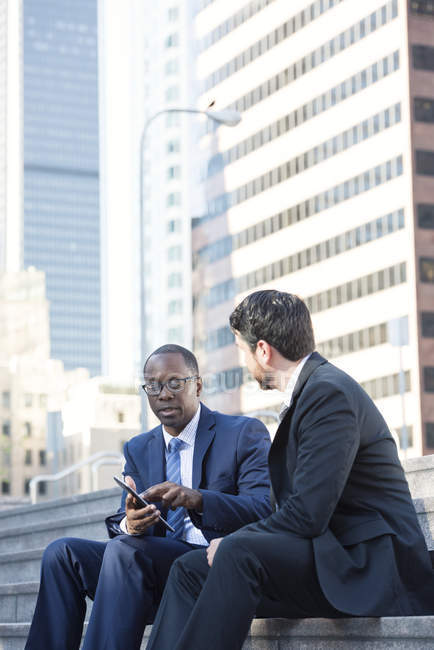 Two businessmen sitting on stairs talking and sharing tablet — Stock Photo