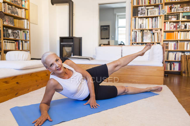 Woman exercising on gym mat in living room — Stock Photo