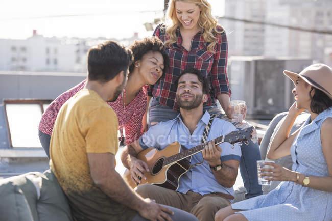 Uomo che gioca chitarra per gli amici alla festa sul tetto, Los Angeles, Stati Uniti — Foto stock