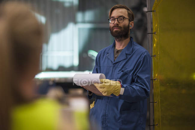 Worker standing with clipboard interacting with co worker in factory — Stock Photo