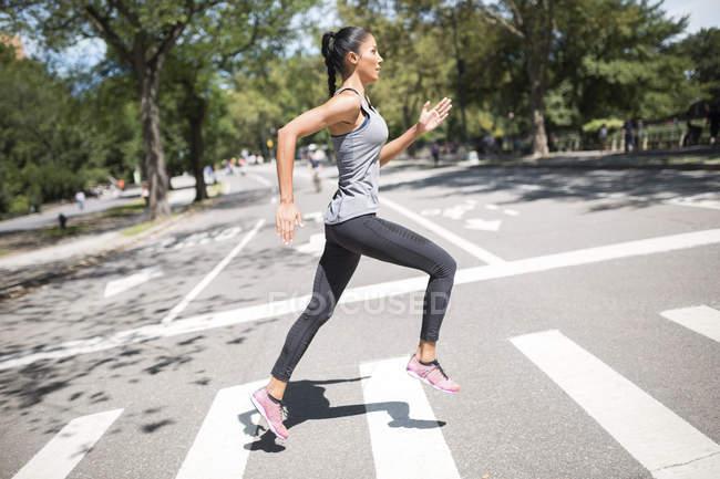 Woman running on zebra crossing — Stock Photo