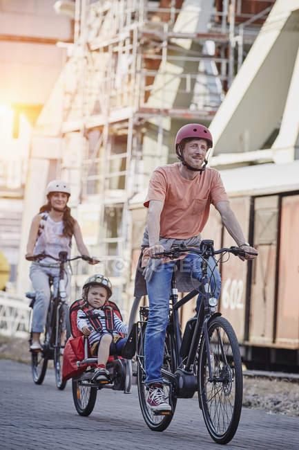 Porträt der Familie Radfahren mit Tochter Trailer — Stockfoto