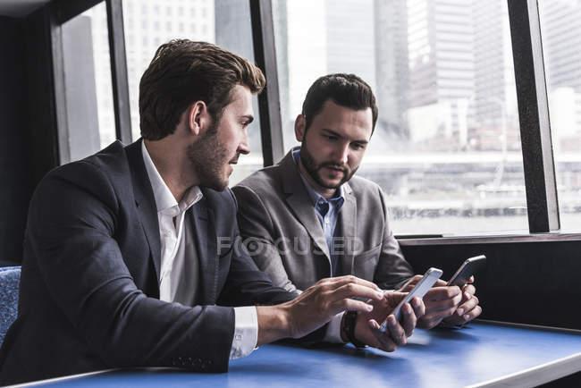 Dois homens de negócios com os celulares falando no convés de passageiros de um ferry — Fotografia de Stock