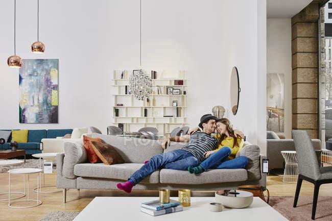 Портрет пары лежащей на диване в мебельном магазине — стоковое фото