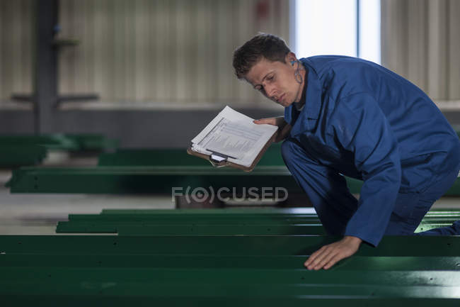 Factory worker inspecting painted steel structure — Stock Photo