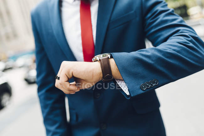 Cropped image of businessman looking on watches — Stock Photo