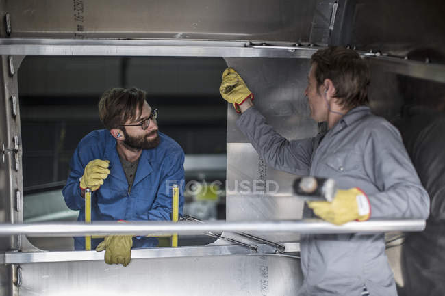 Двоє чоловіків обговорювали всередині контейнера заводі сталеві — стокове фото