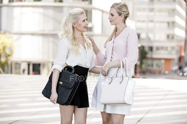Two fashionable businesswomen with bags talking — Stock Photo