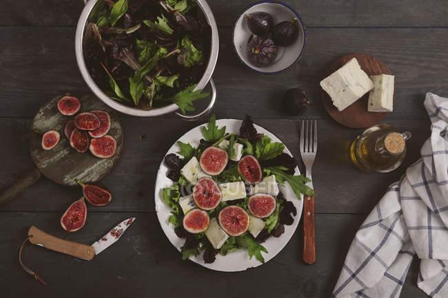 Тарелка смешанного салата с свежий инжир, козий сыр и оливковое масло — стоковое фото