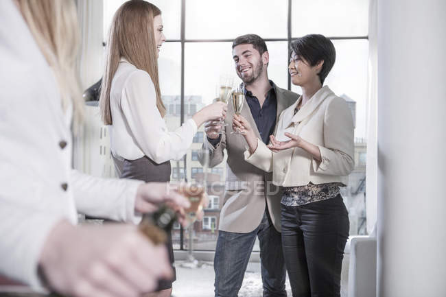 Amis ayant champagne dans un appartement ouvert avec vue sur la ville — Photo de stock
