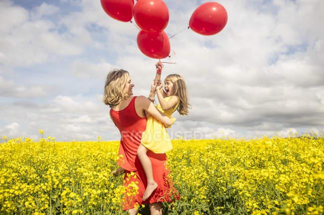 Мати і маленька дочка весело з червоні кулі в гвалтують сферу — стокове фото