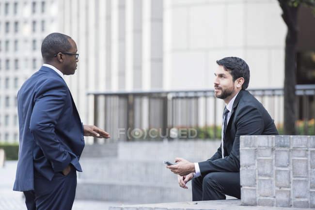 Два уверенно бизнесменов говорить на открытом воздухе — стоковое фото