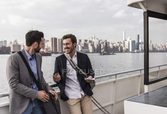 Due uomini d'affari sorridenti che parlano in traghetto sull'East River, New York, USA — Foto stock