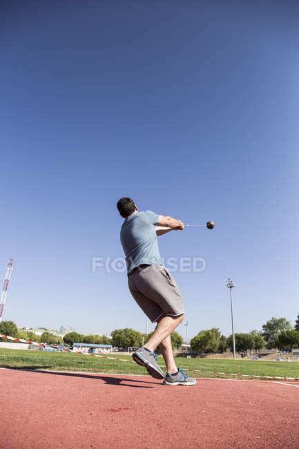 Спортсмен, бросающий молоток на стадионе — стоковое фото