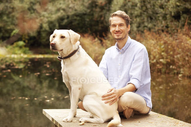 Man with dog on a jetty at a pond in autumn — Stock Photo