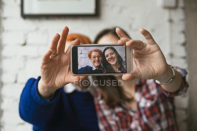 Mutter und Erwachsene Tochter nehmen Selfie auf Smartphone auf couch — Stockfoto