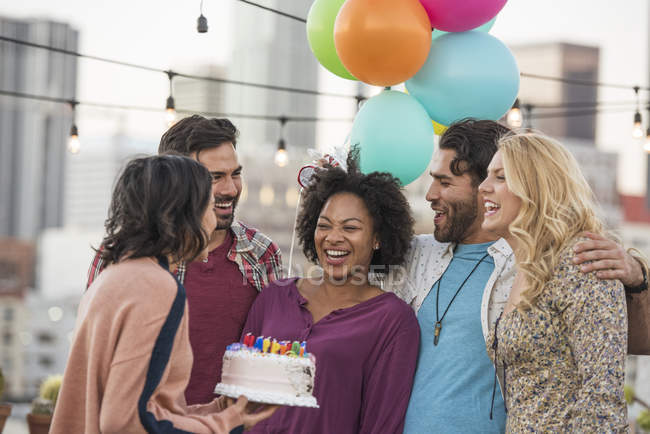 Friends with a birthday cake at rooftop party, Los Angeles, USA — Stock Photo